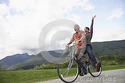 Cheerful Middle aged Couple Bicycling On Country Road