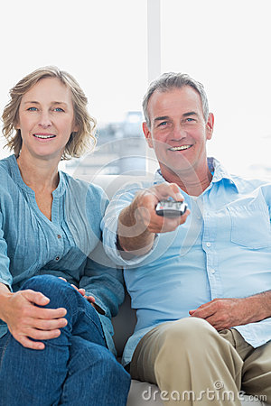 Cheerful Middle Aged Couple Sitting On The Couch Watching