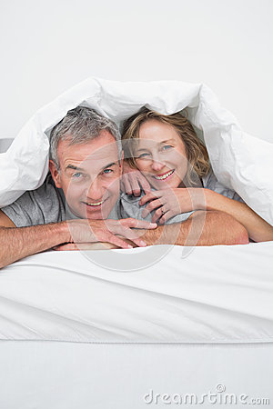 Cheerful middle aged couple under the duvet