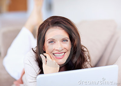 Cheerful middle aged woman with a laptop
