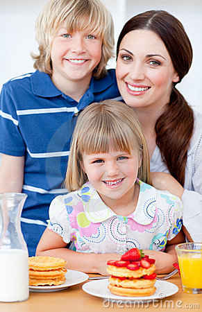 Cheerful mother and her children eating waffles