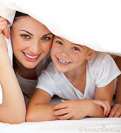 Cheerful mother and her girl playing on a bed