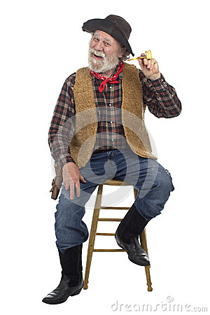 Cheerful old cowboy sits with corn cob pipe