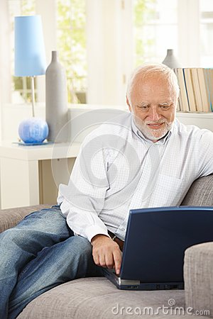 Cheerful pensioner using laptop on couch