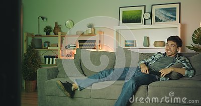 Portrait Of Attractive Asian Guy Watching Tv Having Fun Laughing