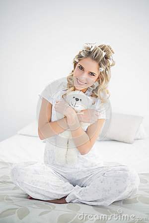 Cheerful pretty blonde wearing hair curlers holding teddy bear