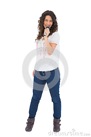 Cheerful pretty brunette with microphone singing