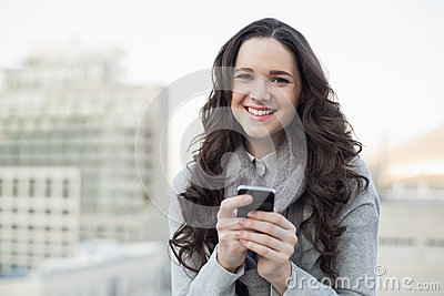Cheerful pretty brunette sending a text on her smartphone