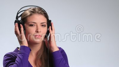 Cheerful pretty woman listening music in headphones stock video footage