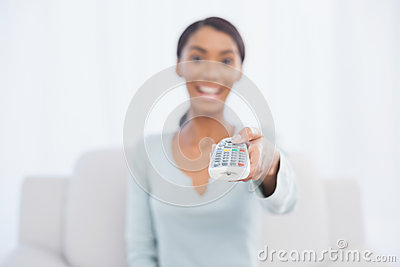 Cheerful pretty woman sitting on sofa changing tv channel