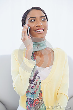Cheerful pretty woman sitting on sofa having a phone call