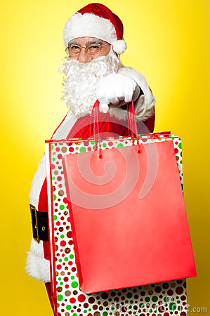 Cheerful Santa holding vibrant colored  bags