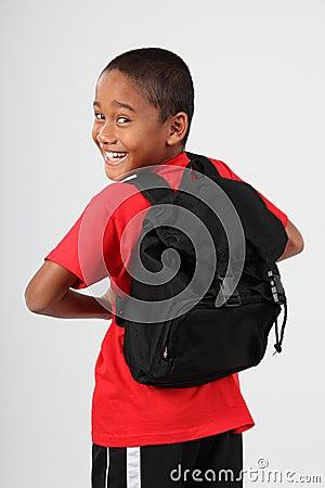 Cheerful school boy looking back over his shoulder