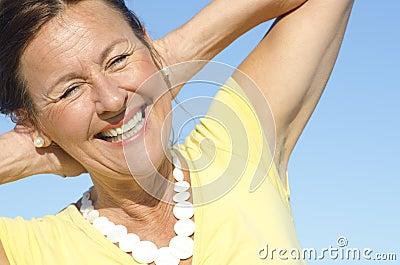 Cheerful senior woman sky background