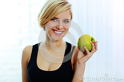 Cheerful smiling fit woman holding green apple