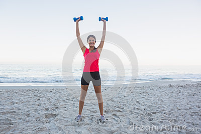 Cheerful sporty woman holding dumbbells