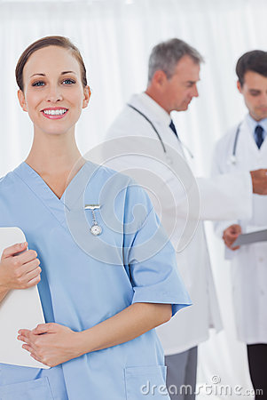 Cheerful surgeon posing while doctors talking on background
