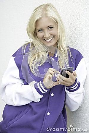 Cheerful teen texting on smartphone