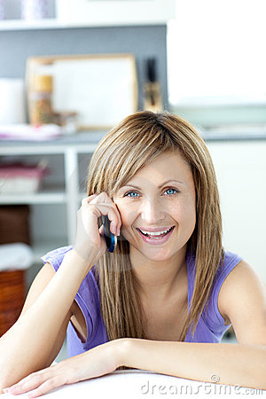 Cheerful woman answering the phone in the kitchen