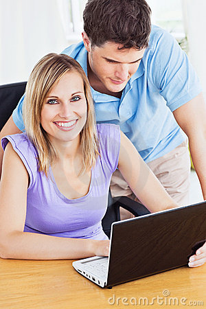 Cheerful woman and her boyfriend using a laptop