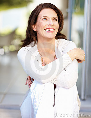 A cheerful woman looking away in thought