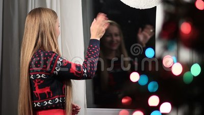 Cheerful woman looking out window and waving hello stock video