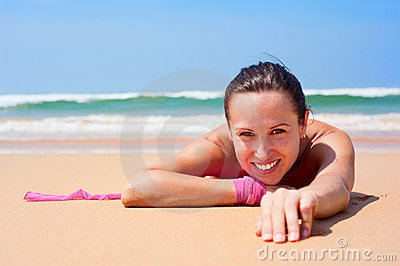 Cheerful woman lying on the wet sand