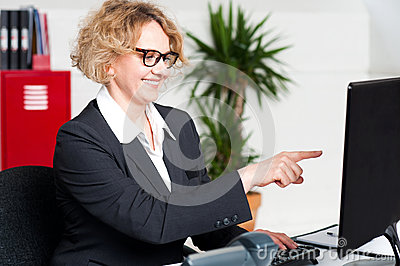 Cheerful woman pointing at computer screen