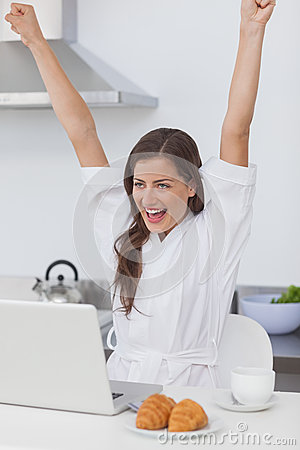 Cheerful woman raising arms while using a laptop