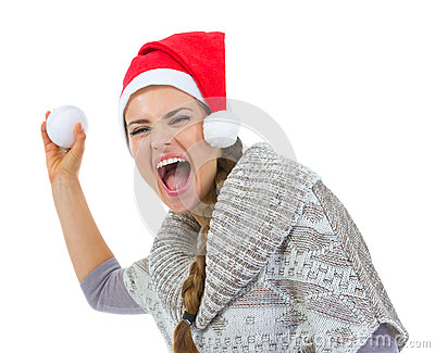 Cheerful woman in Santa hat throwing snowball