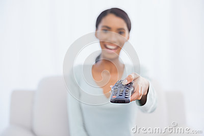 Cheerful woman sitting on sofa changing tv channel