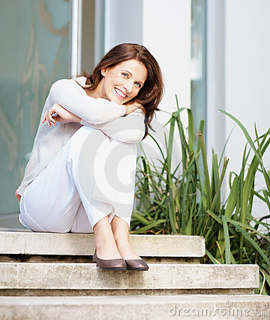 A cheerful woman sitting on steps