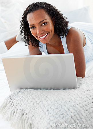 Cheerful woman using a laptop on her bed