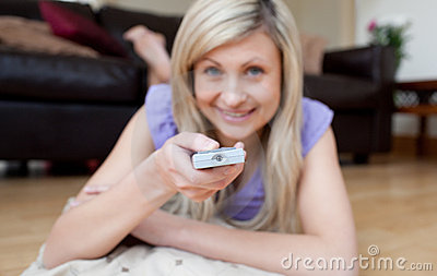 Cheerful woman watching TV lying on the floor