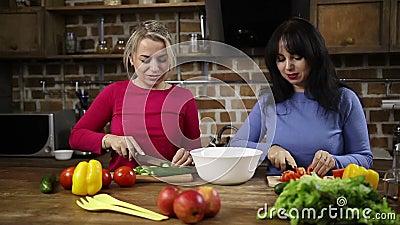 Cheerful women preparing healthy salad in kitchen stock footage