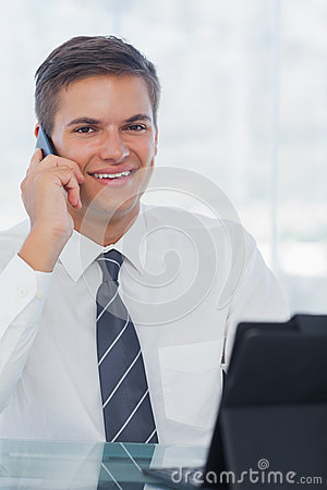 Cheerful young businessman on the phone while working on his tab