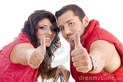 Cheerful young couple showing thumbs up