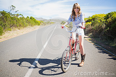 Cheerful young model posing while riding bike
