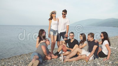 People spending nice time together while sitting on beach, having fun and drinking beer. Cheerful young people spending nice time together while sitting on beach stock footage