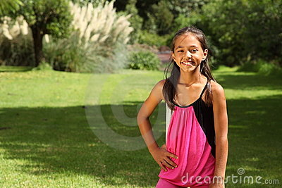 Cheerful young school girl posing in park