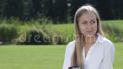Cheerful young woman drinking coffee outside stock footage