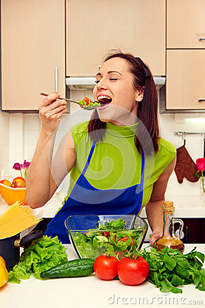 Cheerful young woman eating the salad