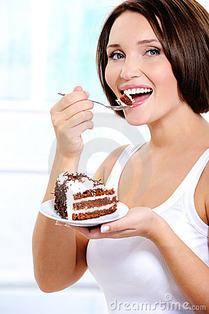 Cheerful young woman eats a sweet cake