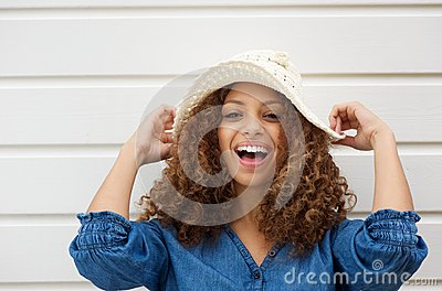 Cheerful young woman with hat laughing outdoors