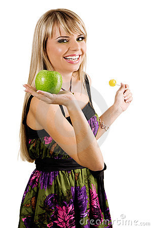 Cheerful young woman holding fresh apple and lolli