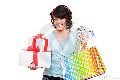 Cheerful young woman holding paper money and gifts