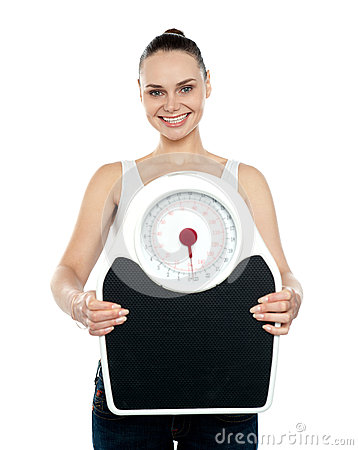Cheerful young woman holding a weighing
