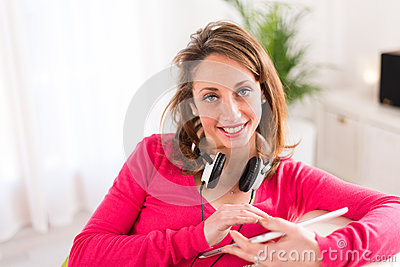 Cheerful young woman at home with tablet compuer