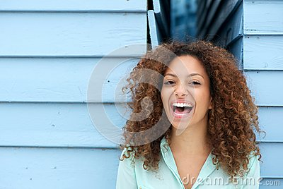 Cheerful young woman laughing outdoors