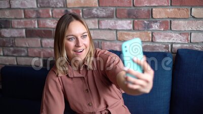 Cheerful young woman talking video chat using mobile phone and waves hand. Cheerful young woman talking video chat using mobile phone and waves her hand for stock video